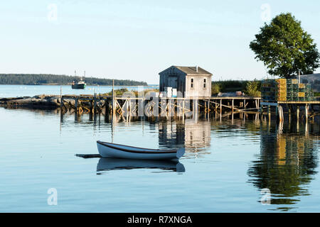 View of Bass Harbor Maine from the deck of Thurston's Lobster pound with a dock, lobster traps, boat house, tree and row boat reflections visible. - Stock Photo
