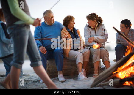 Group of multi-generational people toasting marshmallows beside a campfire on a beach. - Stock Photo