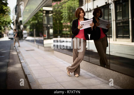 Side view of a stylish woman reading a newspaper. - Stock Photo