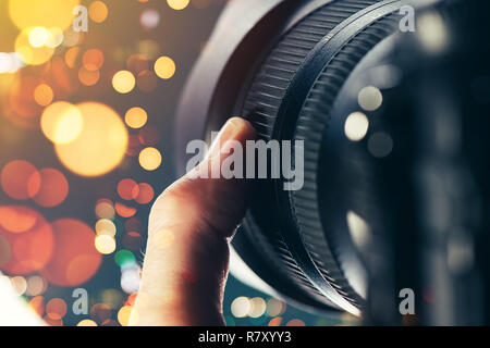 Photographer using zoom lens on DSLR camera, close up of finger rotating the ring on photographic equipment part - Stock Photo