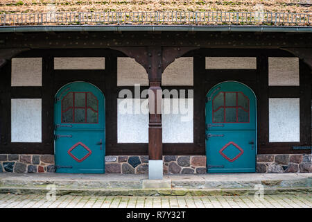 Vintage round shaped doors painted blue and red with etched glas panels in a half-timbered house - Stock Photo