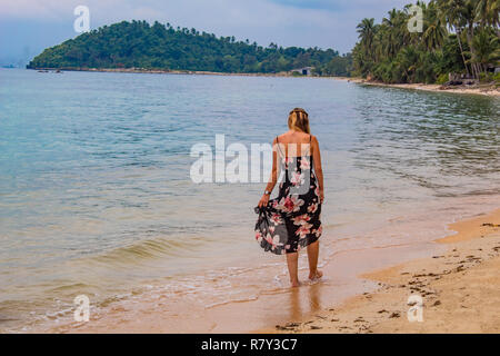 Backview of Woman with long sundress walking on the beach - Stock Photo