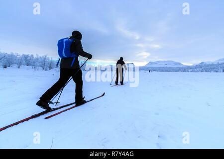 Sweden, Lapland, region listed as World Heritage by UNESCO, Norrbotten County, Nordic Skiers in Abisko National Park with Laporten in the background3 - Stock Photo