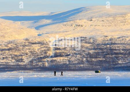Sweden, Lapland, region listed as World Heritage by UNESCO, Norrbotten County, View of skiers at sunrise on Lake Tornetrask in the vicinity of Abisko National Park - Stock Photo