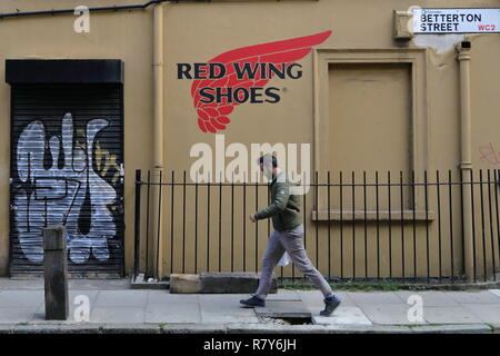 Walking men on the one of the central streets of London. Summer time and small graffiti saying 'red wings shoes' drawn on the wall. - Stock Photo