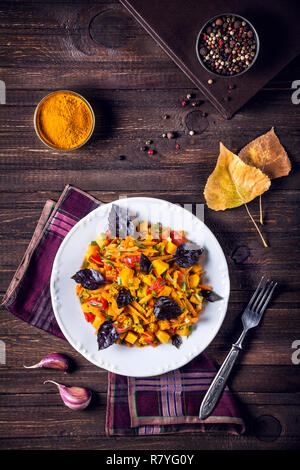 Autumn salad with pumpkin, carrot, tomato and basil on the wooden table with spices in the kitchen - Stock Photo