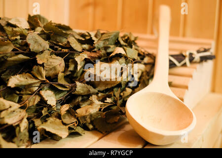 Sauna accessories close up in traditional finnish or russian sauna, birch broom and wooden scoop. Rest and relaxation in the spa to keep warm in the cold winter - Stock Photo