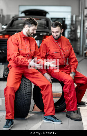 Car service workers in red uniform having a break sitting together on the wheels at the tire mounting service - Stock Photo