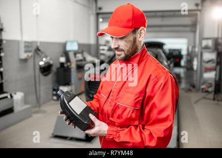 Portrait of a handsome auto mechanic in red uniform holding bottle with engine oil at the car service - Stock Photo