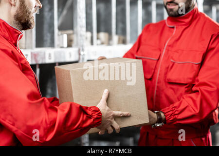 Worker in red uniform holding package in the warehouse, close-up view - Stock Photo