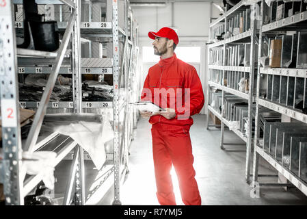 Warehouse worker in red uniform checking goods standing with clipboard in the storage with metal shelves - Stock Photo