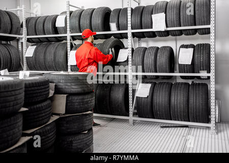 Worker or salesman taking tires from the shelves of the warehouse of the car service - Stock Photo