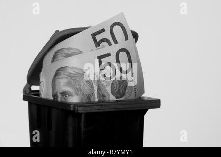 Australian fifty dollar notes in a trash bin in black and white. - Stock Photo