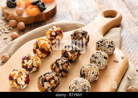 Homemade energy balls are lying in rows on kitchen cutting board on wooden table.