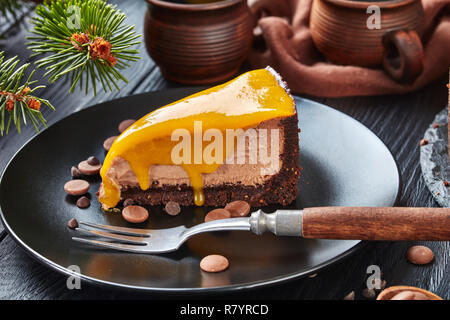 close-up of a piece of a chocolate mango cheesecake served on a black plate with dessert fork and chocolate chips. fir tree and cups with coffee at th - Stock Photo