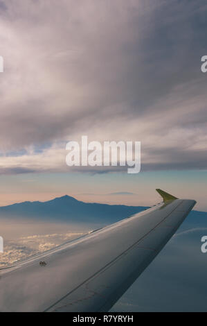 View from the air of the volcano Teide on the island of Tenerife seeing the profile of the island of La Palma in the background, all framed by an airp - Stock Photo