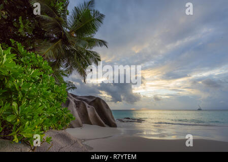 Picturesque sunset on dream beach at anse georgette on praslin on the seychelles. A big granite rock, turquoise water, palm trees and a romantic sky.. - Stock Photo