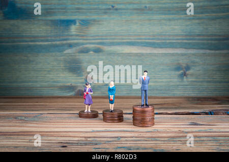 Miniature people standing on piles of coins - Stock Photo