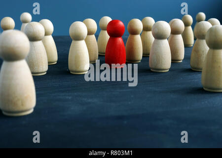 Wooden figures and one red figure. Be different. Stand out from the crowd. - Stock Photo