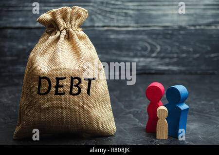 A bag of money with the word Debt and the family. The concept of debt for property. Mortgage. Real estate, home savings, loans market concept. Risks o - Stock Photo