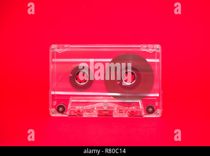 Audio tape on red background conceptual image - Stock Photo