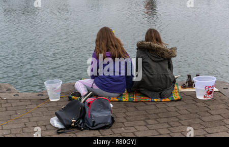 Lymington, England - October 25, 2018: Crab fishing by two girls in the harbor of Lymington with two small buckets and some bags. - Stock Photo