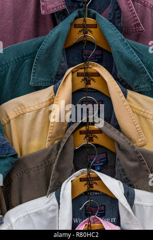 Lymington, England - October 25, 2018: Different shirts and colors hanging on clothes hooks at a shop. - Stock Photo