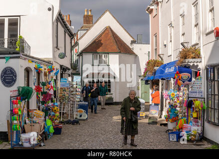 Lymington, England - October 25, 2018: Old lady walking in the street with touristic shops and white houses in typical English street. - Stock Photo