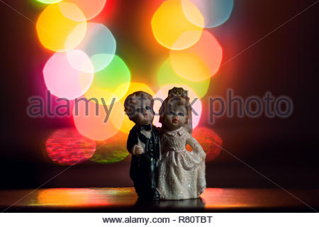 Cute Miniature bride and groom figurines with bokeh in background. - Stock Photo