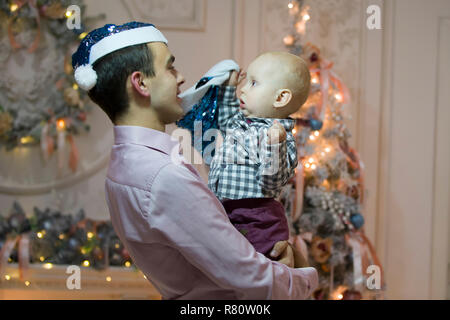 Father and son on New Year's Eve. Baby on the hands of dad in Santa Claus hats - Stock Photo