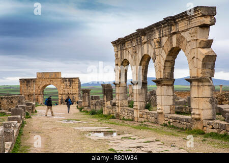Morocco, Meknes, Volubilis Roman site, three arches on Decumanus Maximus, to Triumphal Arch of Caracalla - Stock Photo
