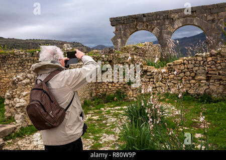 Morocco, Meknes, Volubilis Roman site, visitor photographing three arches on mobile phone - Stock Photo