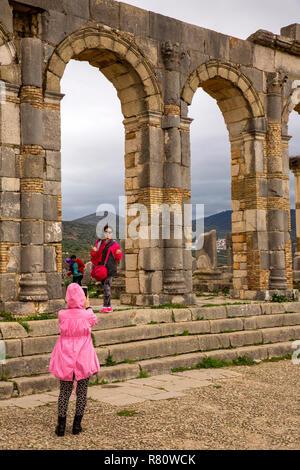 Morocco, Meknes, Volubilis Roman site, visitors taking souvenir photograph in the Basilica - Stock Photo