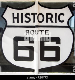 Tucumcari NM / United States - July 18, 2016: giant Route 66 Highway symbol painted sign on a defunct and abandoned gas station shop window - Stock Photo
