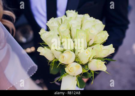 wedding bouquet with white flowers in the hands of the groom. - Stock Photo