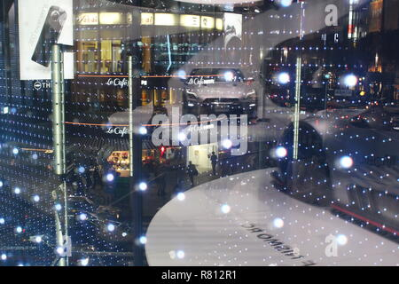 Overhead view of a junction in Ginza including the iconic Sanai Dream Center with Nissan cars reflected in a showroom window. - Stock Photo