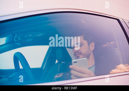 Shot of a handsome man using mobile phone while driving. - Stock Photo