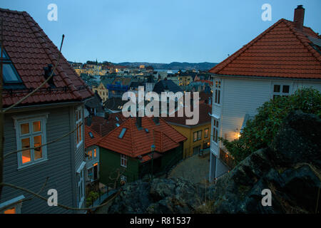 View of Bergen picturesque old town on the hill at dusk. Traditional wooden houses, tiled roofs, lanterns, cityscape. Landmark of Norway. - Stock Photo