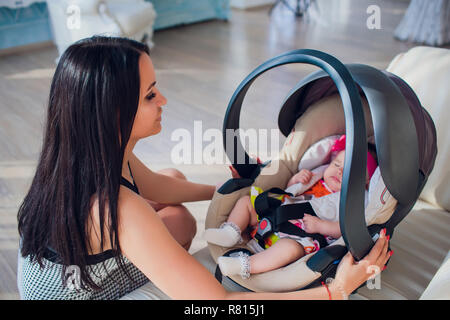 family, transportation, security, car trip and people concept - happy mother fixing baby girl in baby seat at home - Stock Photo
