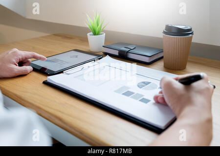 businessman going through some paperwork and signing a document at desk in office - Stock Photo