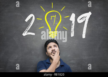 Thinking Position of A Young Asian Man while standing against blackboard with chalk drawing of light bulb and new year 2019 - Stock Photo