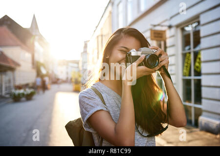 Smiling young Asian woman taking photos in the city - Stock Photo