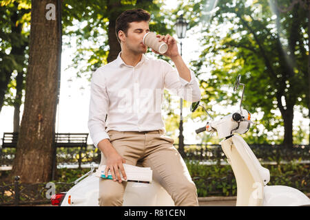 Happy young businessman sitting on a motorbike outdoors, reading newspaper, drinking coffee - Stock Photo