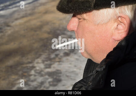 An elderly gray-haired man in winter clothes holding a cigarette in his mouth - Stock Photo