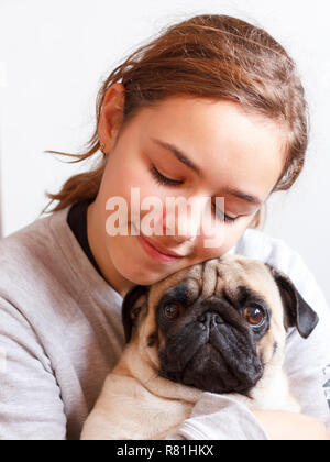 Happy pretty smiling teenager girl hugging cute pug dog with love - Stock Photo