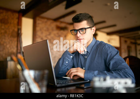 Thoughtful young caucasian businessman in glasses working on laptop computer. Pensive attractive hipster freelancer thinks over the solution of the problem with computer in cafe. Business concept. - Stock Photo