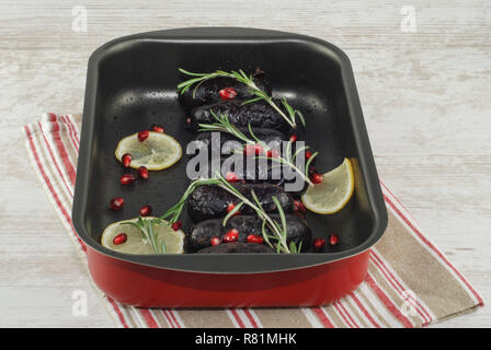Baked in oven blood pudding sausages in baking dish with seasoning and rosemary. Czech, German, Estonian, British traditional Christmas Festive Dinner - Stock Photo