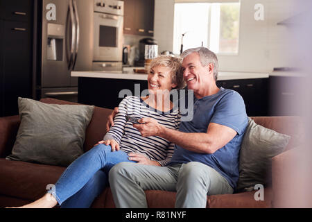 Senior white couple relaxing on couch watching television - Stock Photo
