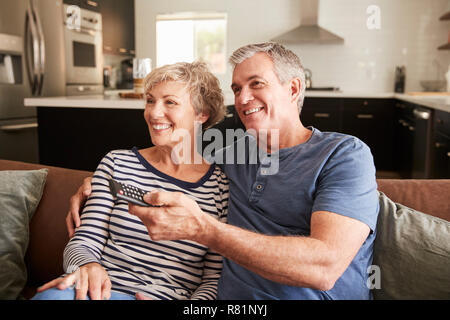 Senior couple sitting on couch watching television, close up - Stock Photo