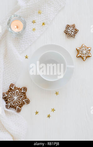 Christmas background. Empty white cup, gingerbread, candles and knitted scarf on a white wooden background. Light still life. Flat lay, top view, copy - Stock Photo